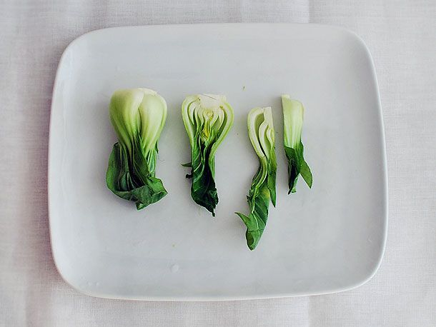 A plate with fresh bok choy, some of it cut in half.