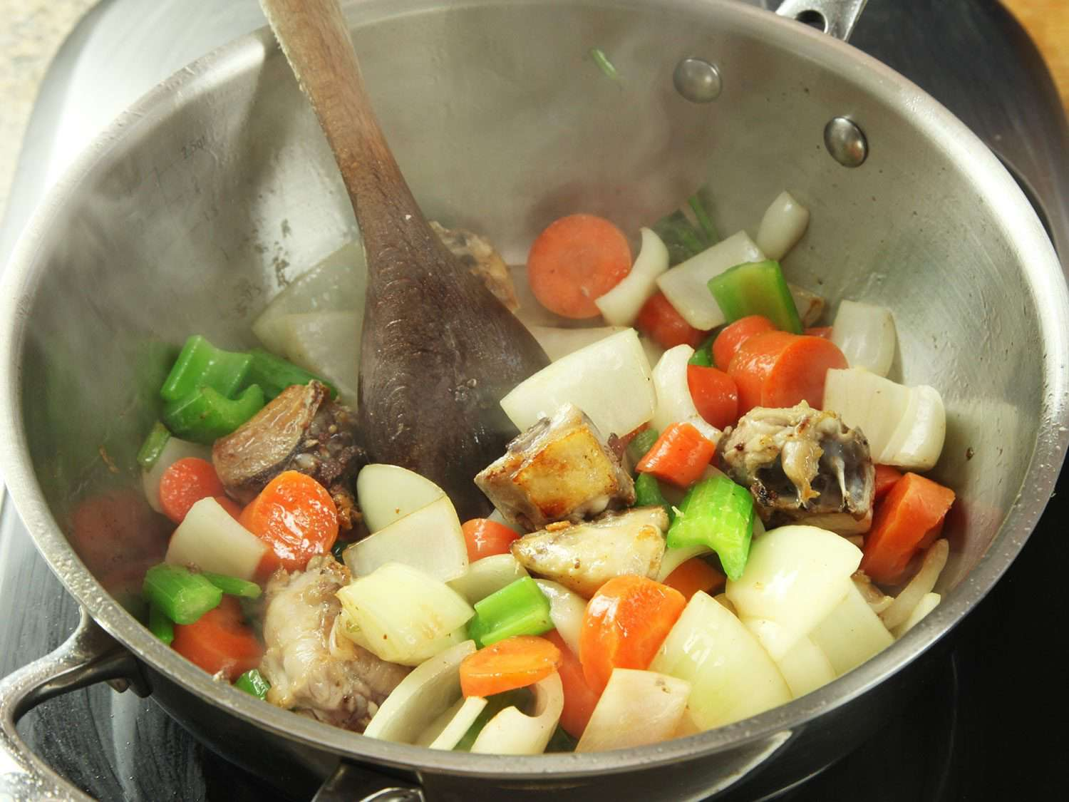 Vegetables and chicken back pieces sautéing in pan to make jus.