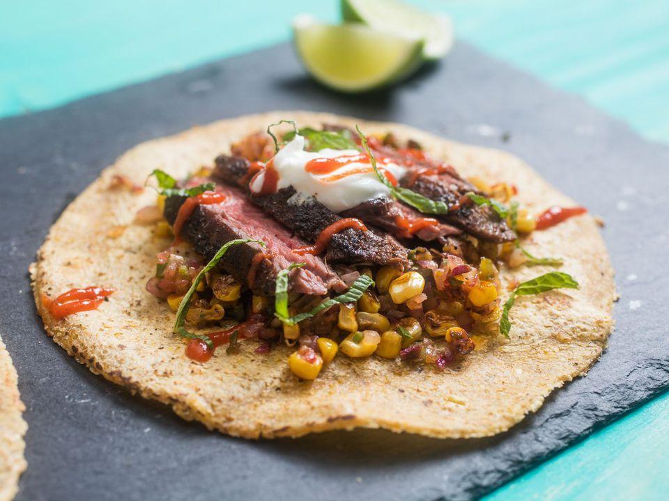 steak and corn taco on a slate board