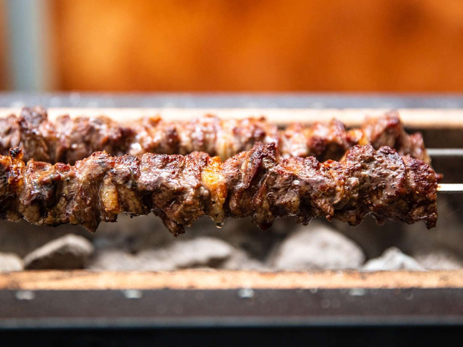 Closeup of lamb skewers grilling over coals on a Japanese konro grill