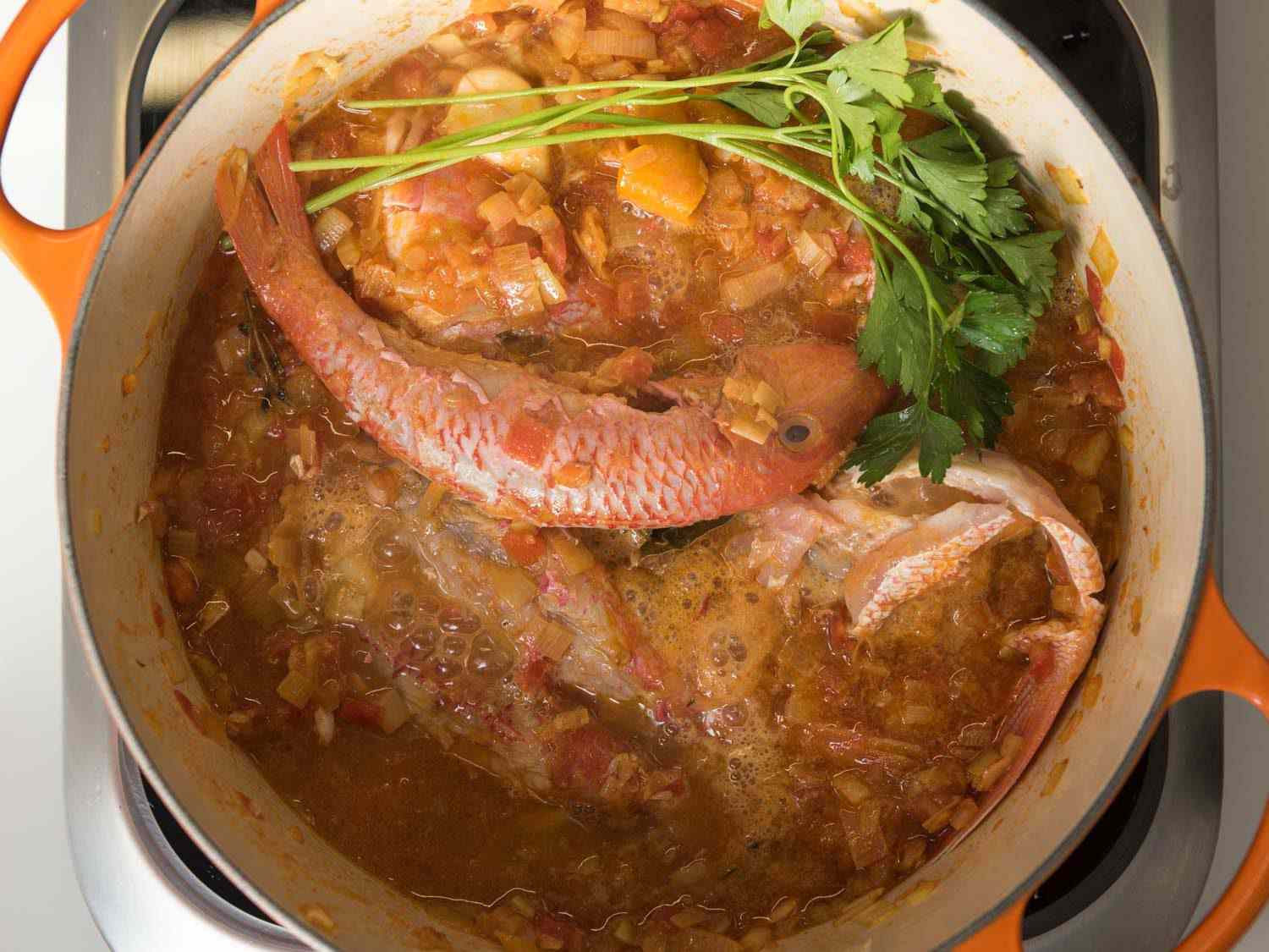 A pot of fish and fish bones in the pot with herbs for bouillabaisse