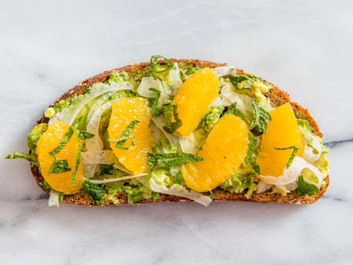 Avocado toast with orange slices and shaved fennel.