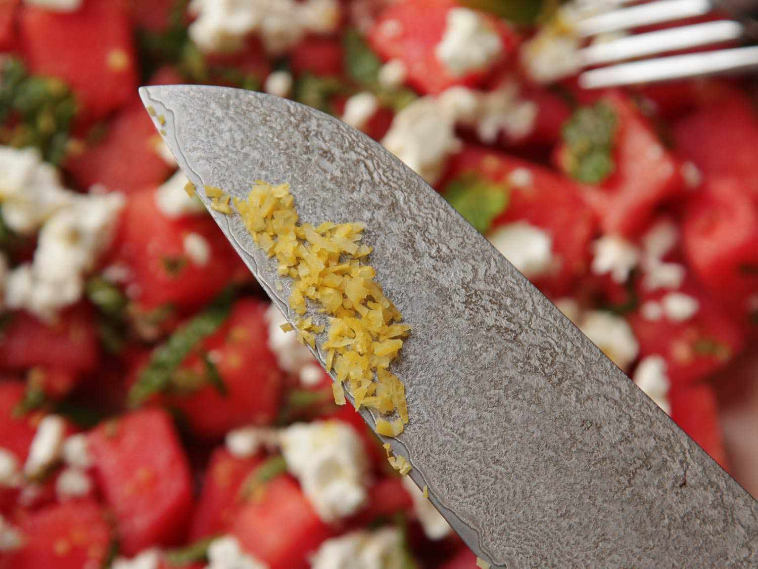 Chopped lemon zest on the blade of a chef's knife, with watermelon, feta, and mint salad in the background.