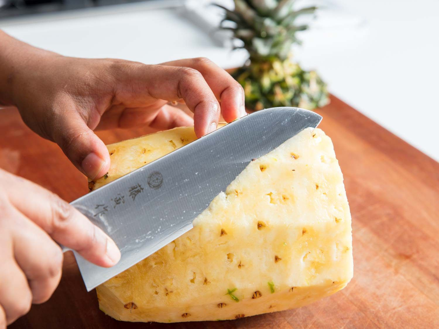A knife starting to trim the eyes out of a pineapple.