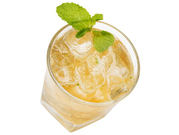A glass of whiskey smash garnished with a fresh mint sprig.