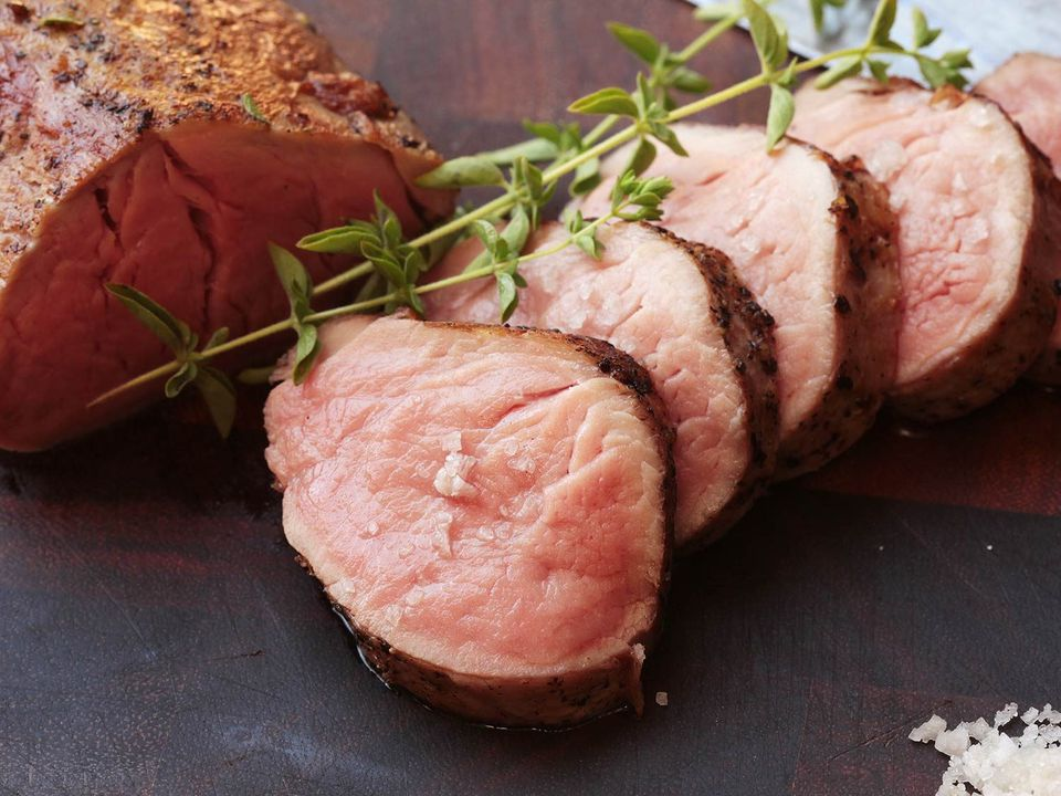 Sous vide pork on serving board with herbs.