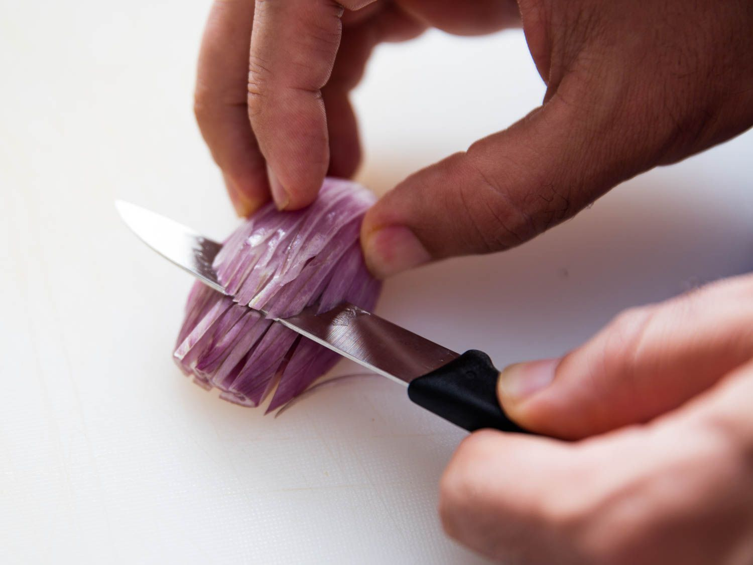 Mincing a shallot with a paring knife.