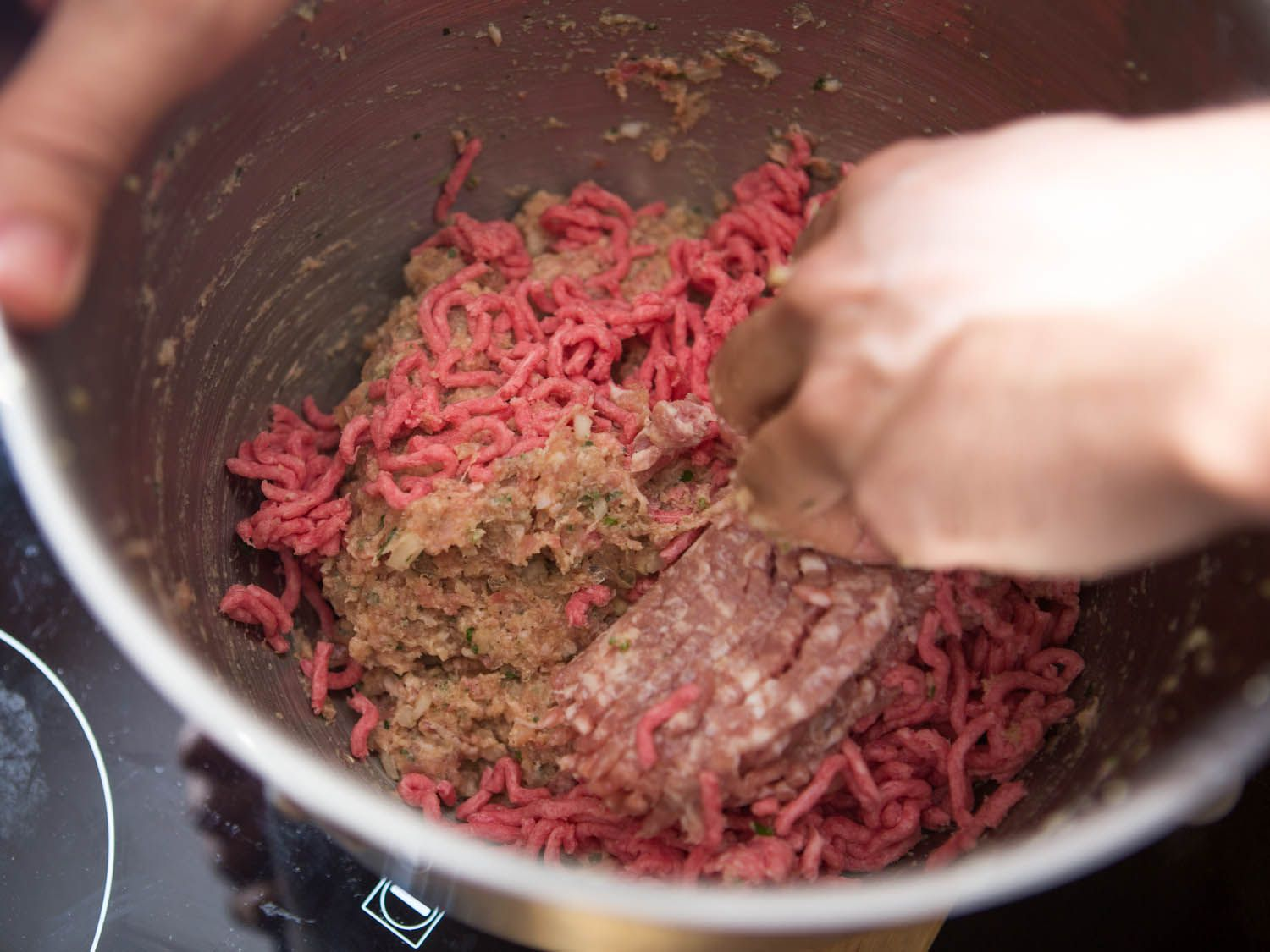 Using hands to mix in ground meat to emulsified meat and flavorings mixture for meatballs.