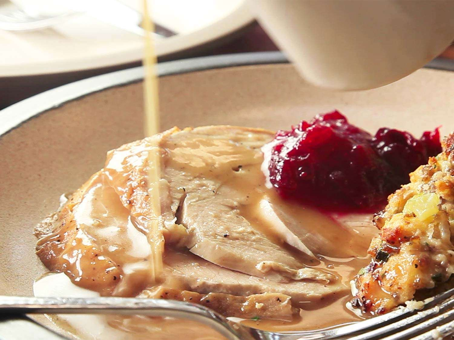 Pouring gravy from a pitcher over a plate of sliced roast turkey meat, cranberry sauce, and dressing.
