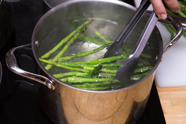 Asparagus being blanched in a large stock pot filled with water. Someone is removing the asparagus with a pair of tongs.
