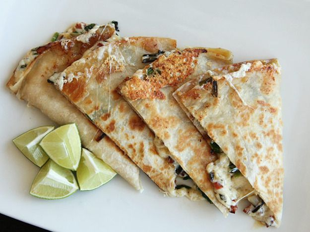 Ramp and chorizo quesadillas cut in wedges on a plate with lime wedges.