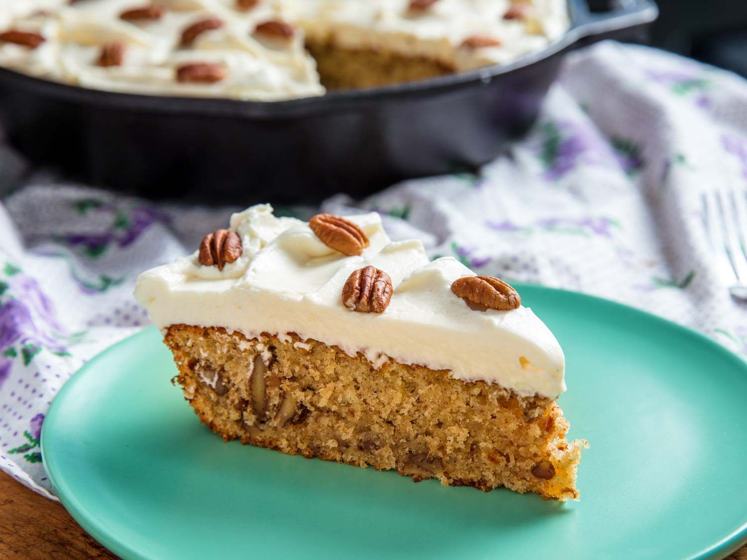Slice of hummingbird cake topped with pecans and cream cheese frosting