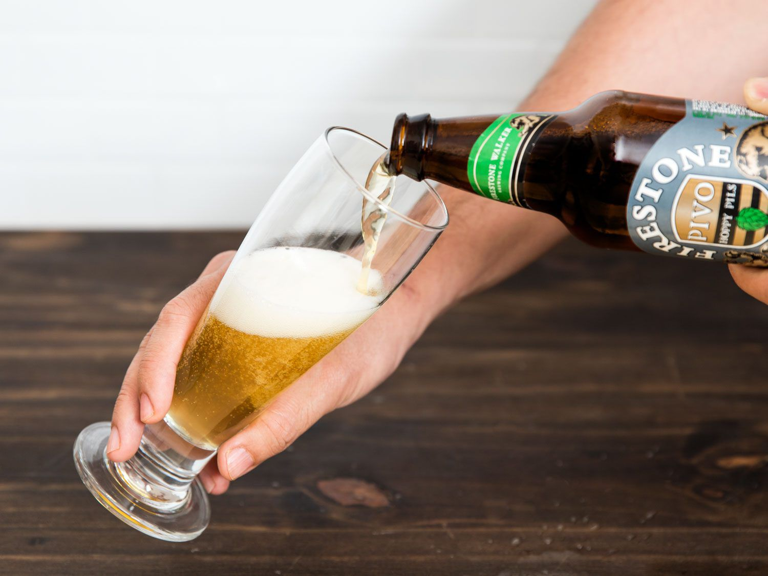 Pouring beer into a glass.