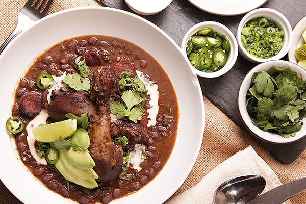 Bowl of black bean soup with large pieces of meat, avocados, and jalapenos on top.