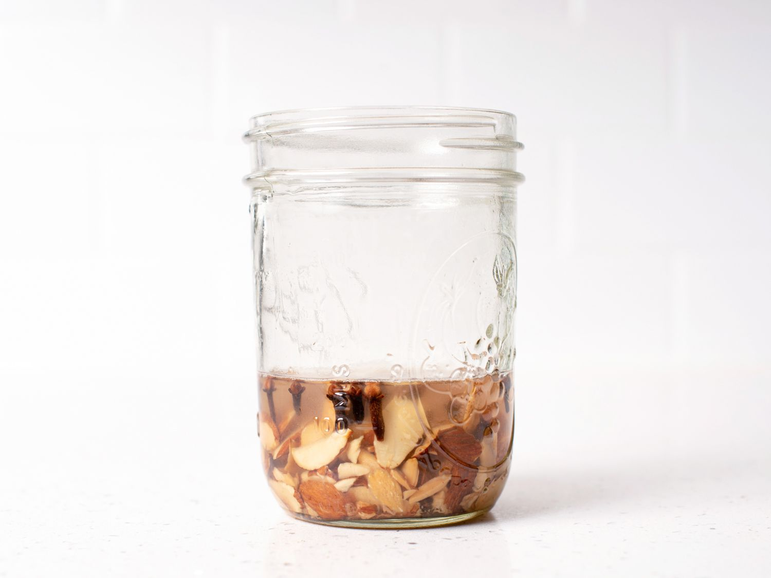 toasted almonds, cloves, and rum in a jar, ready to steep