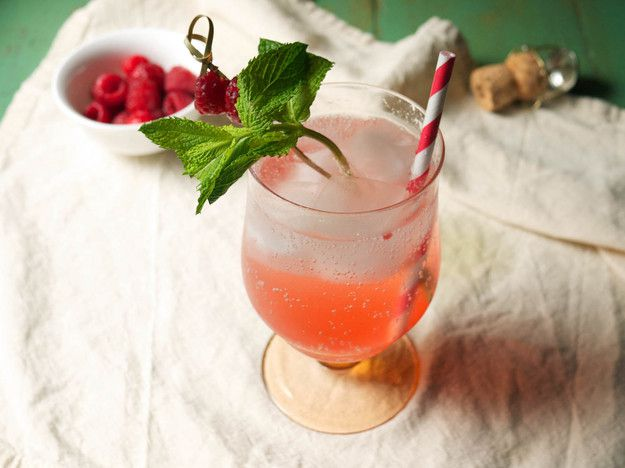 A Raspberry Spritz in a glass, garnished with mint and a straw.