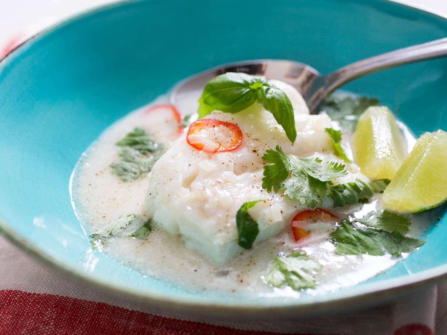 Cod à la nage in coconut milk in a bowl, with lime wedges, cilantro, and chile slices.