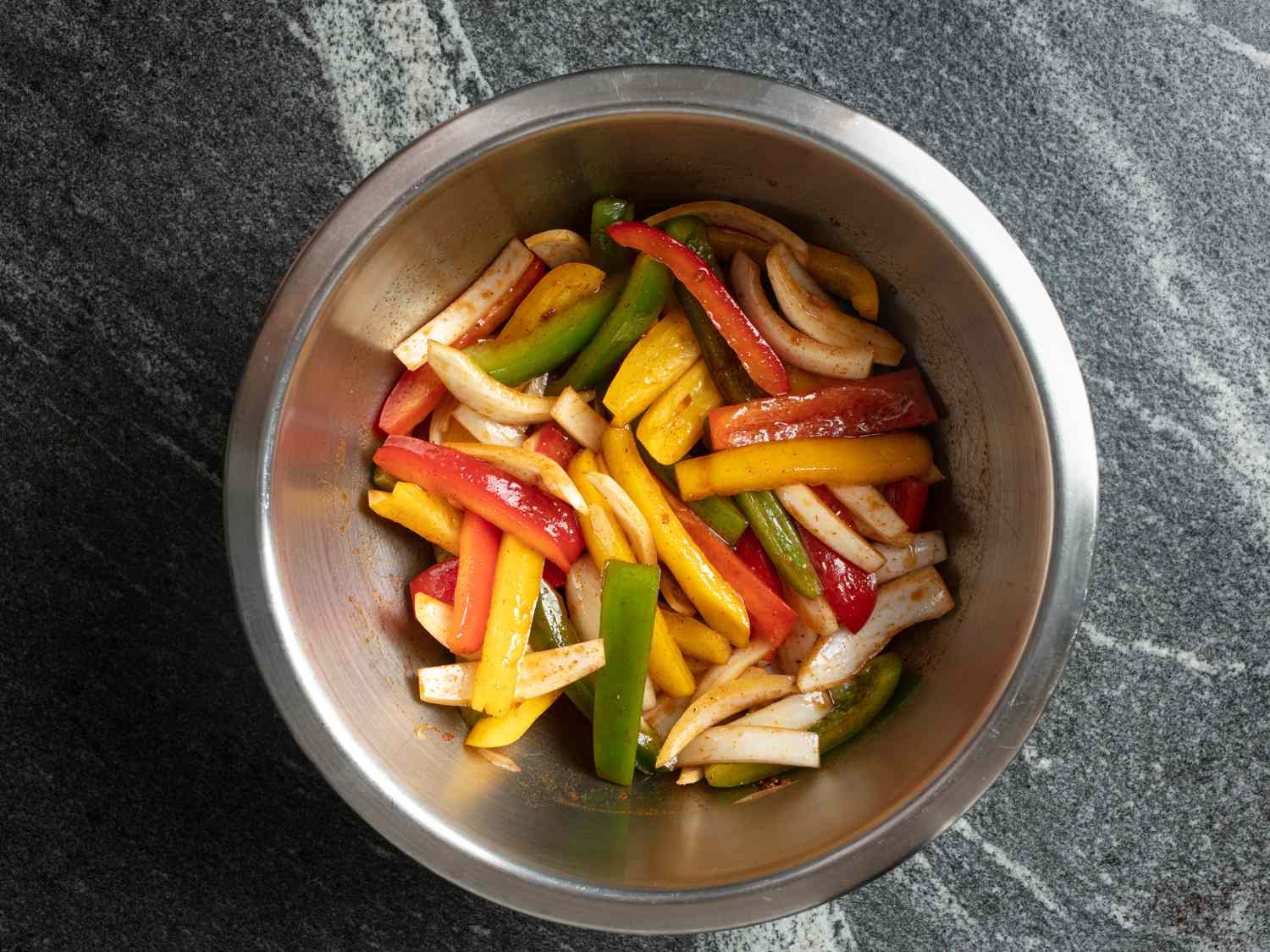 Metal bowl filled with sliced peppers, onions, and fajita marinade.