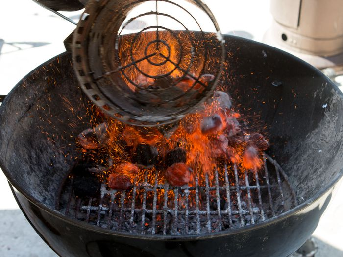 a chimney starter adding charcoal to the base of a grill