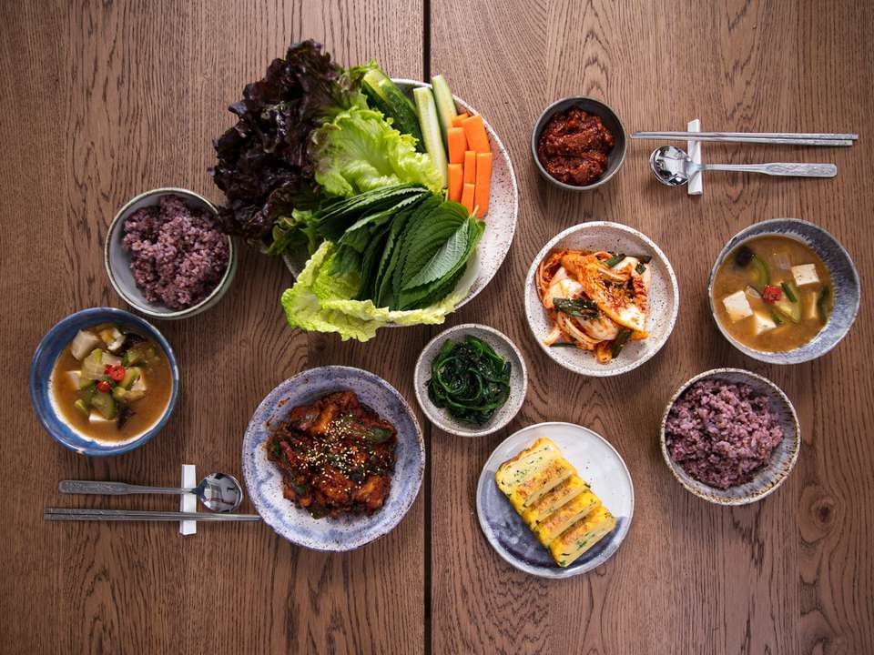 Full spread of a Korean meal on a table shot from overhead, with banhan, rice, soup, a main dish and a basket of tender lettuces