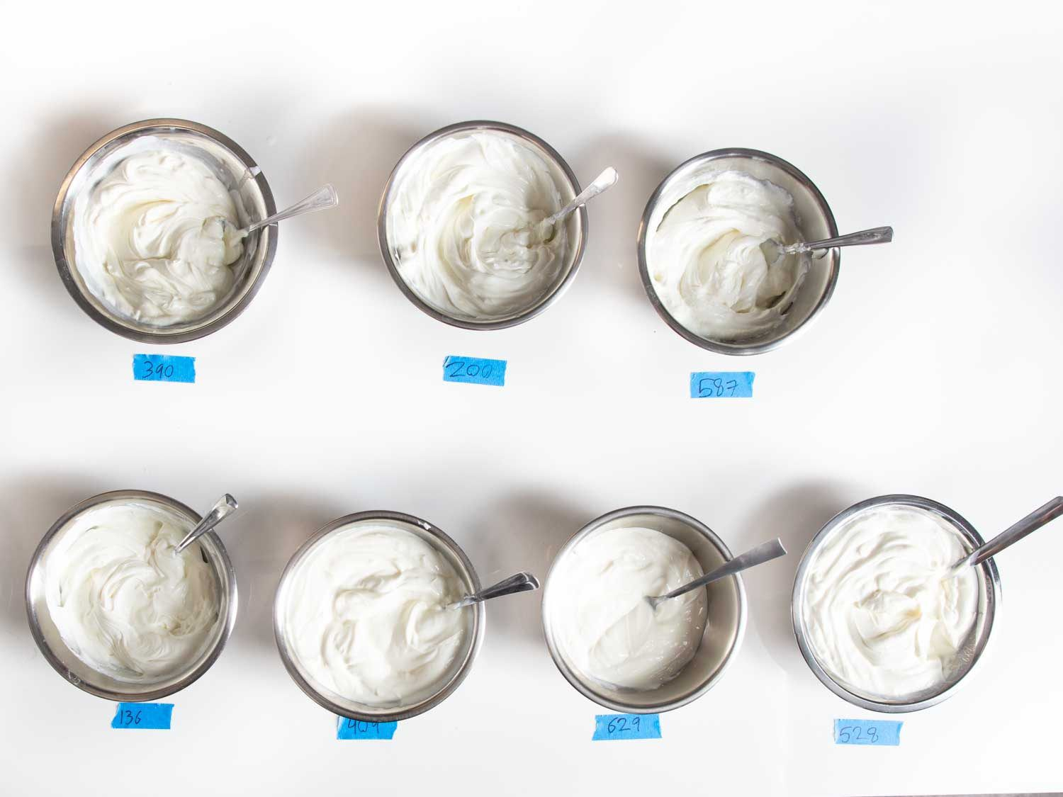 Overhead shot of seven dishes of Greek yogurt to be tasted, each with a spoon stuck inside, and a numbered blue label placed beneath each one