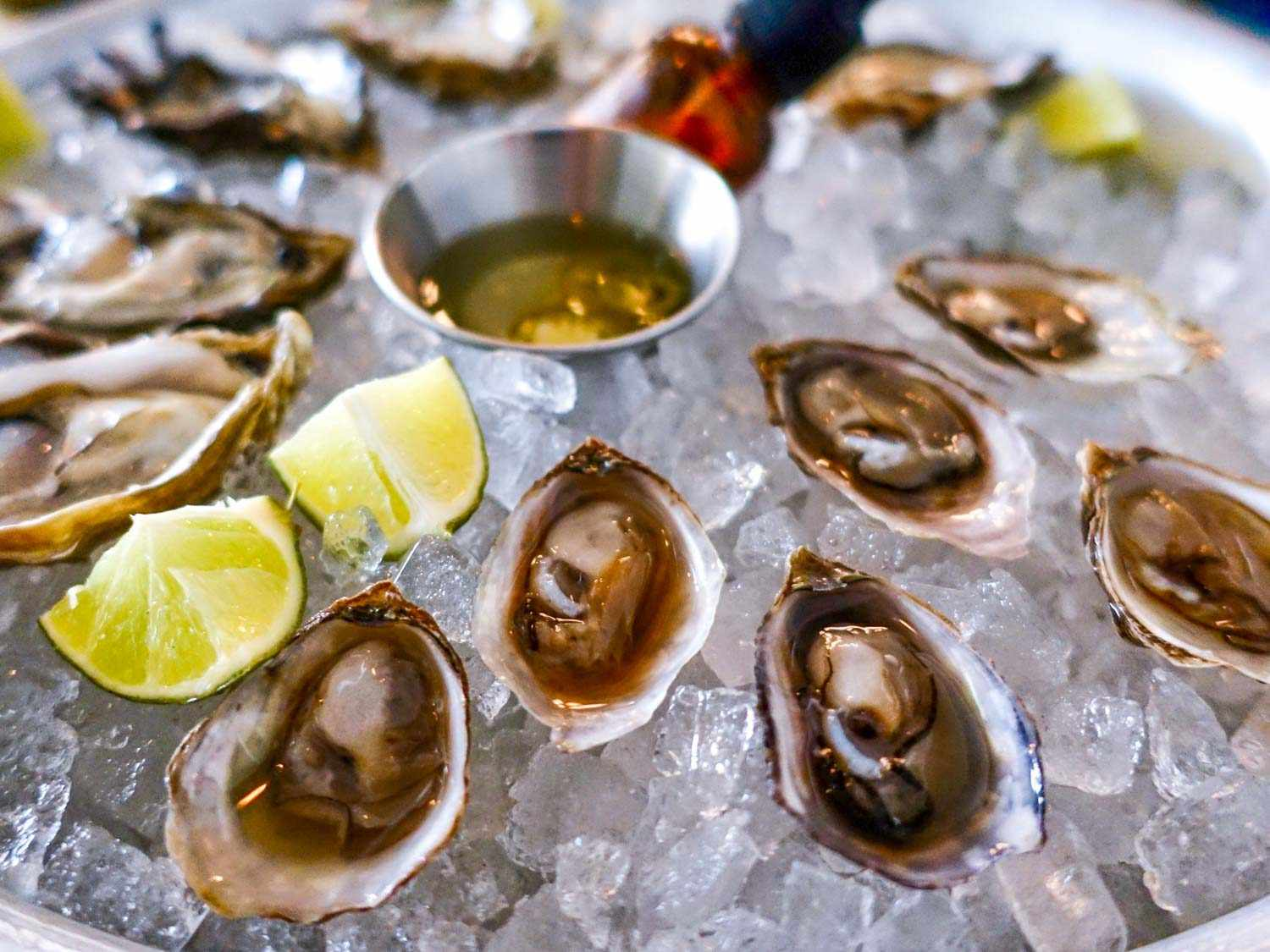 A plate of Olympia oysters on the half-shell, on ice, with lime wedges
