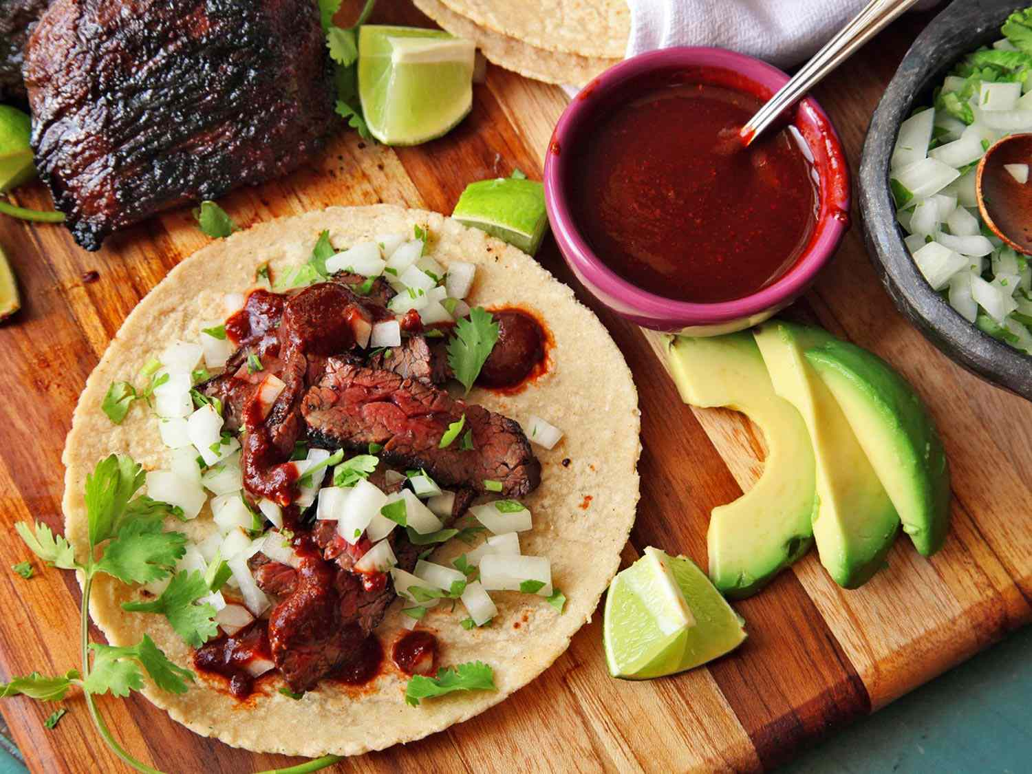 A carne asada taco made with grilled medium rare steak, chopped onion, cilantro and red salsa, plated on a wooden cutting board with additional steak and toppings surrounding it.