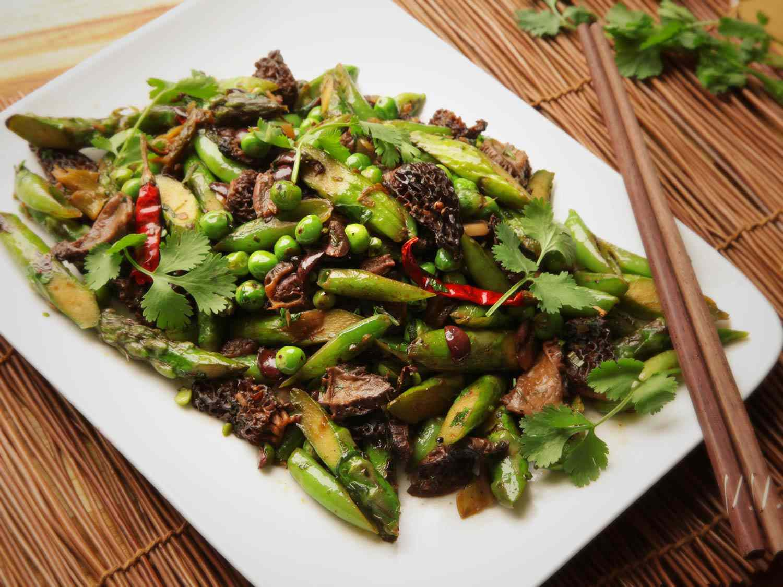Stir-fried asparagus, English peas, snap peas, morel mushrooms, and black olives on a white plate