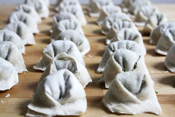 Array of uncooked wontons on a wooden cutting board.