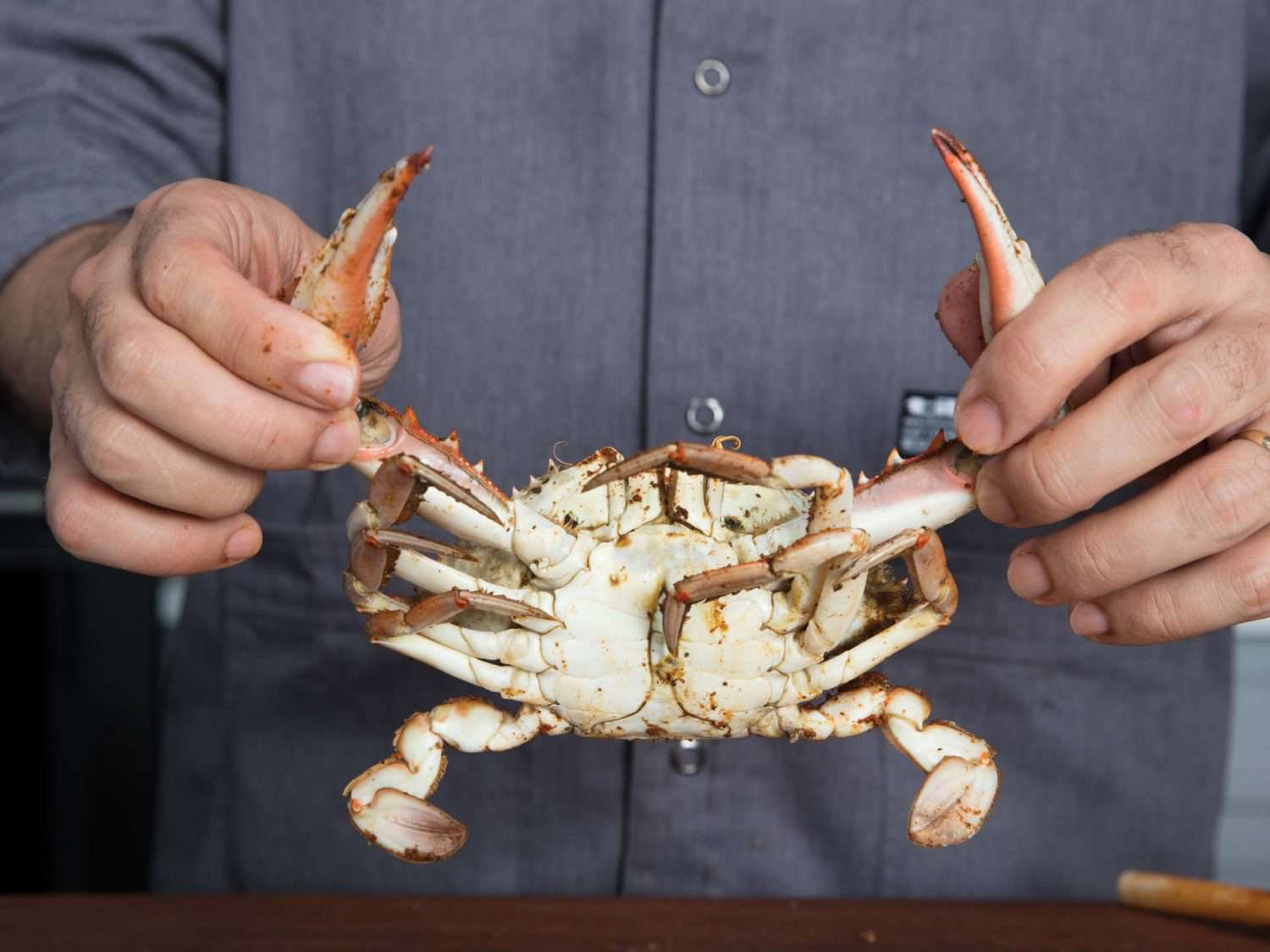 Pulling off the legs of a cooked crab