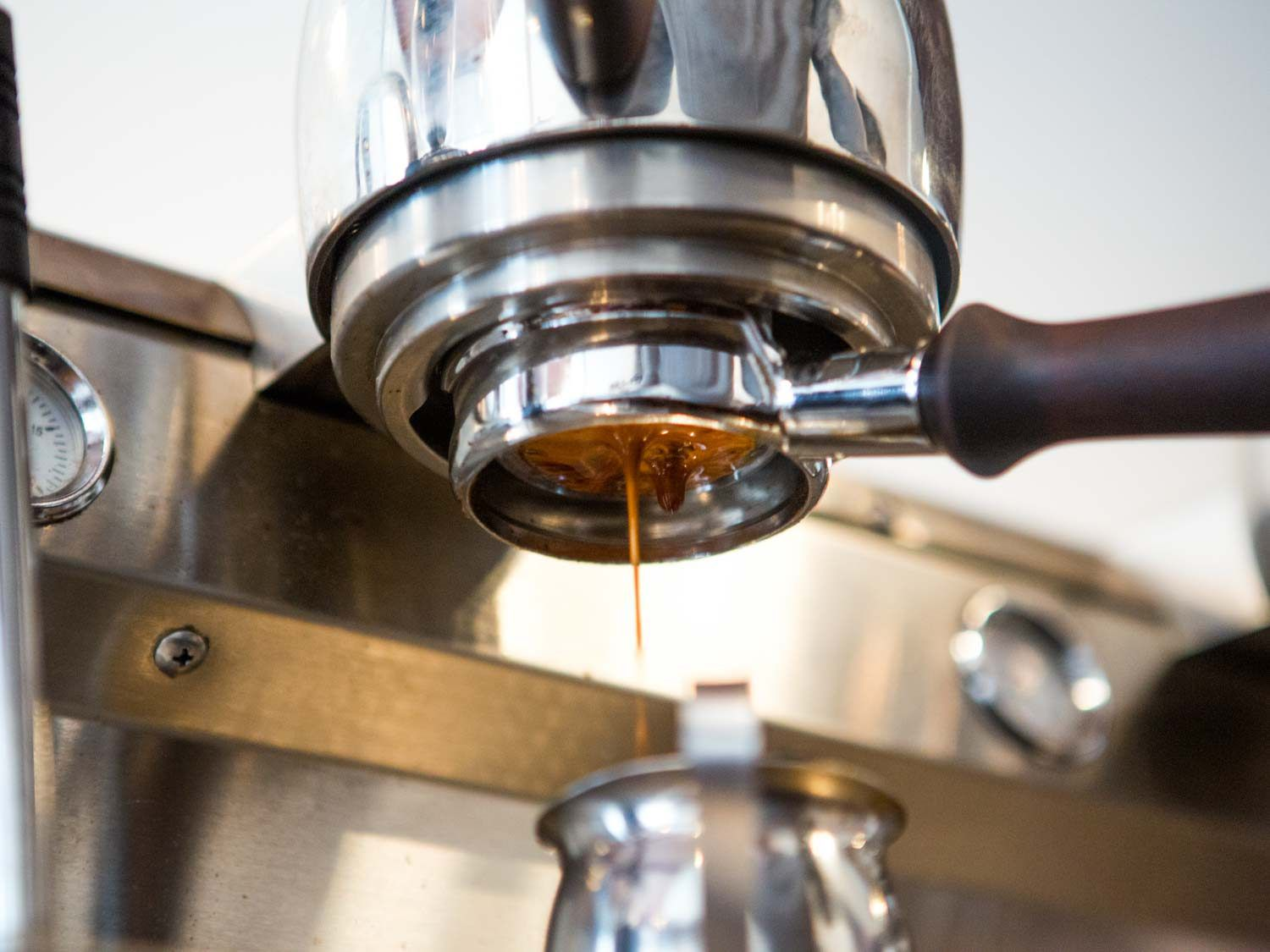 Espresso pours from the machine's portafilter into a small pitcher