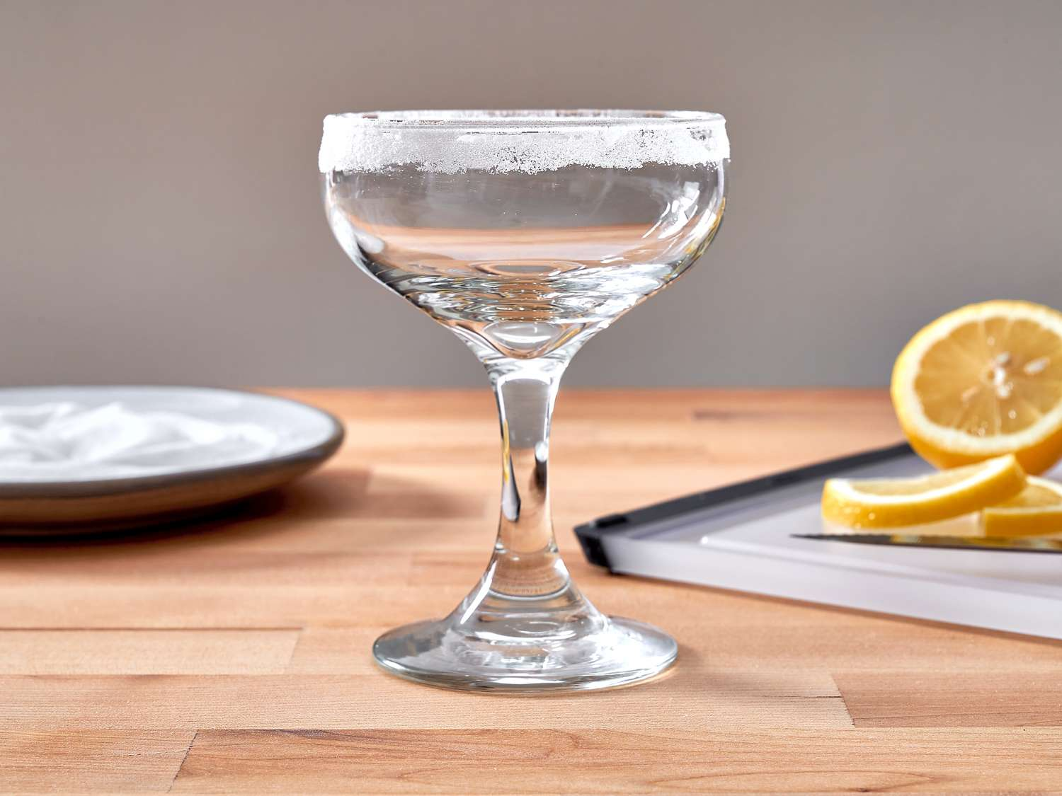 a coupe glass with a salt rim, orange slices behind