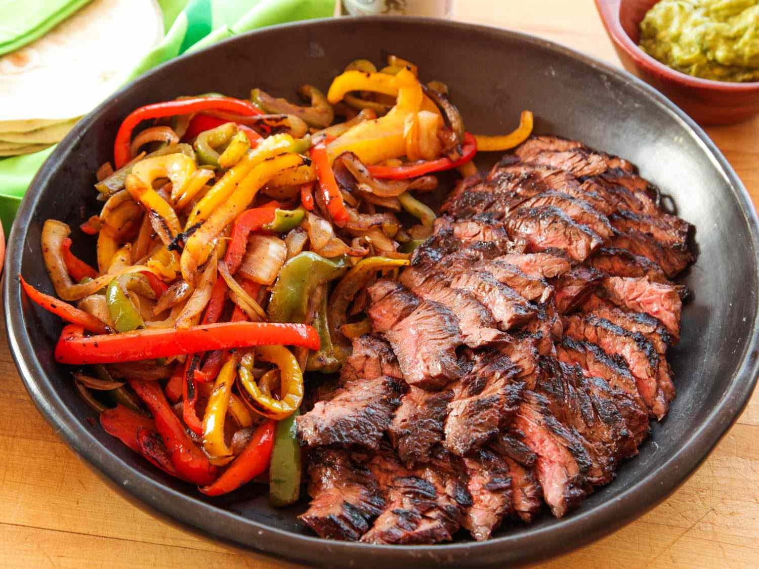 A bowl full of cooked peppers and onions and grilled sliced steak for fajitas, with tortillas and guacamole visible in the background.