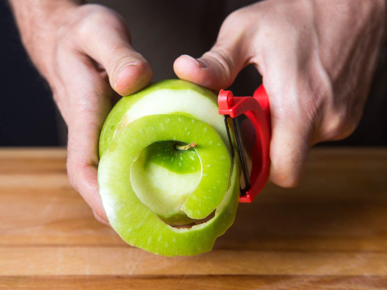 A pair of hands peeling curls of skin off an apple, using a Y-peeler
