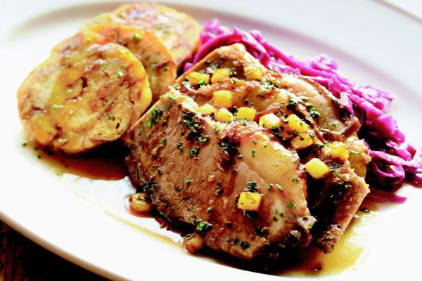 a plate of beef sauerbraten with red cabbage and pretzel dumplings.