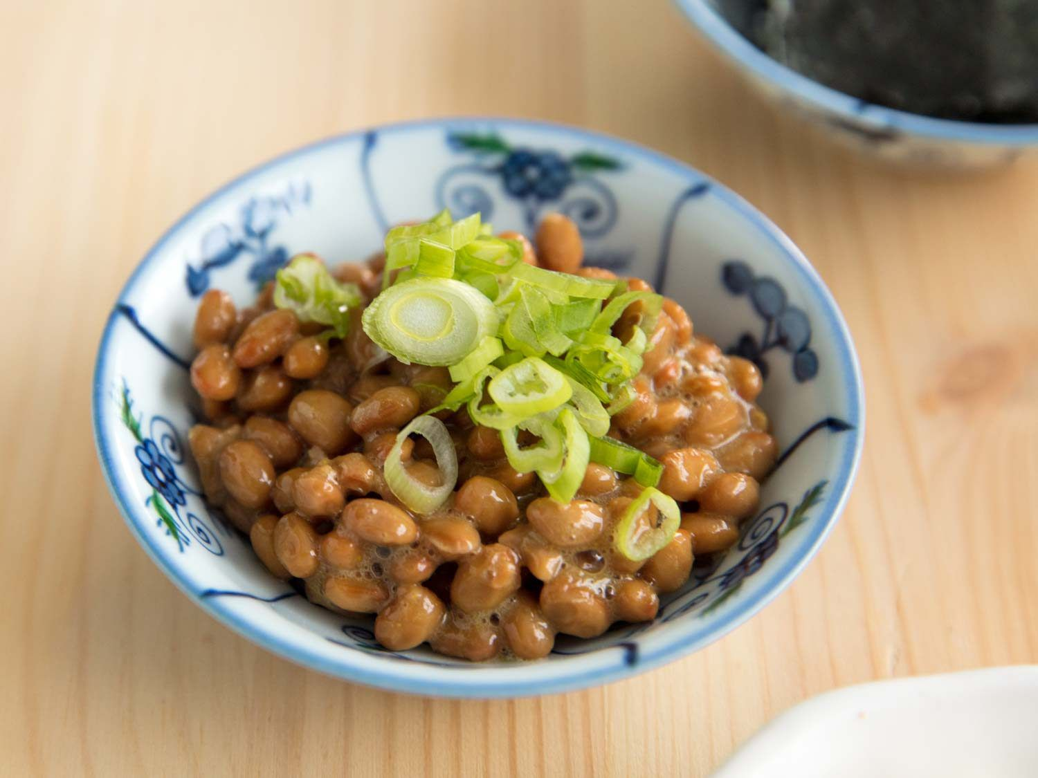 Natto in a ceramic bowl, topped with sliced scallions