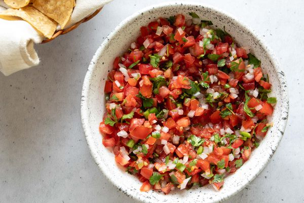 a bowl of pico de gallo with tortilla chips on the side