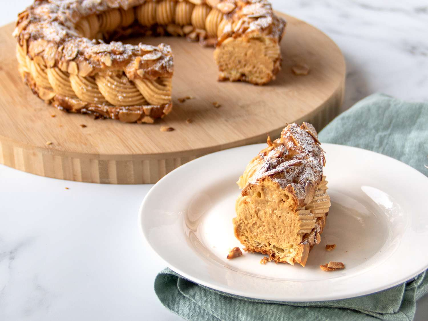 a slice of Paris-brest on a plate with the rest in the background
