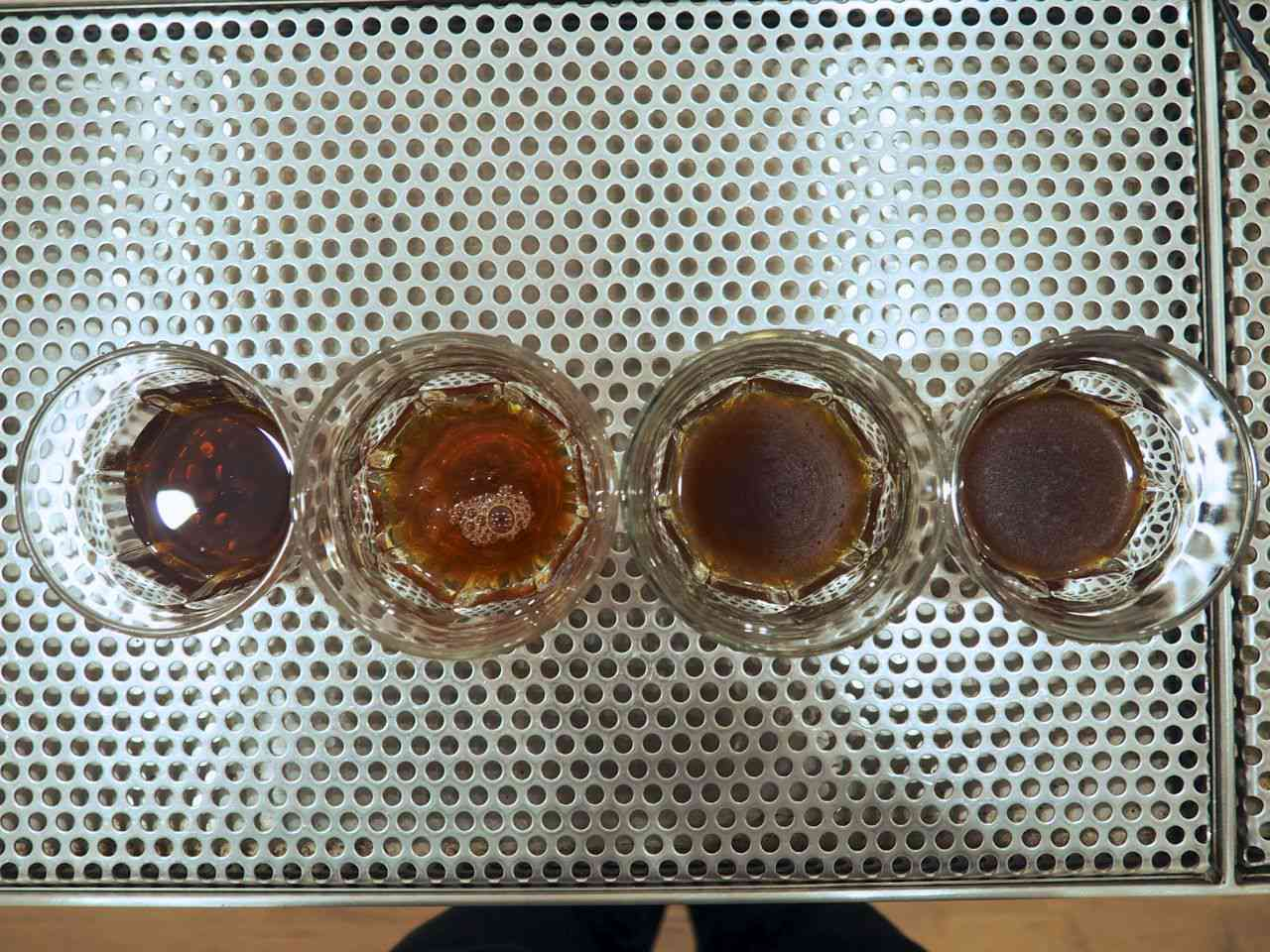 Iced coffee prepared in four different ways, all served in small glasses.