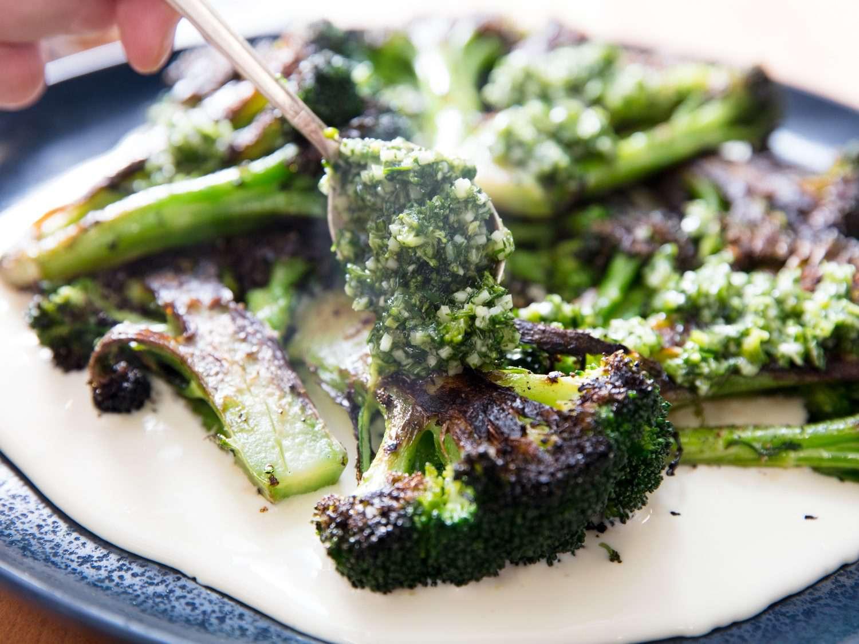 Spooning gremolata over charred broccoli.
