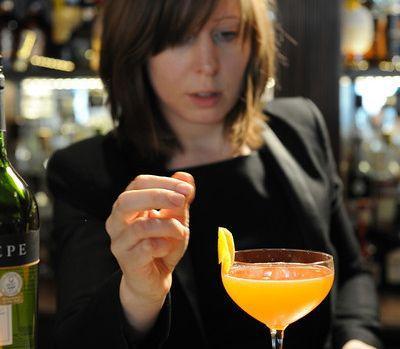 bartender adding garnish to cocktail