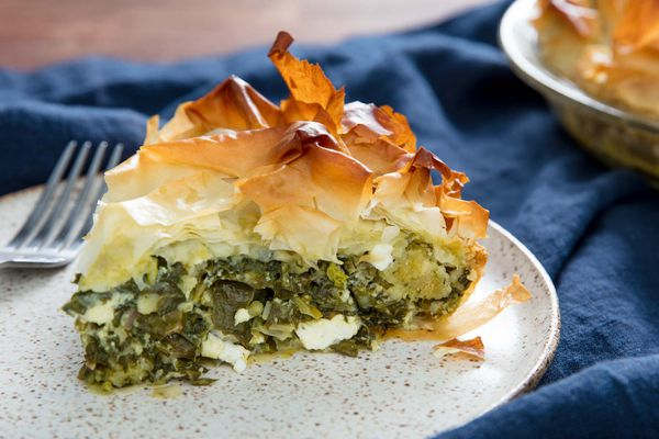 A wedge of spanakopita on a speckled white plate with a fork.