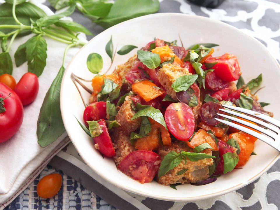 Close-up of finished panzanella (tomato and bread salad) in a white dish, next to ripe tomatoes and basil sprigs
