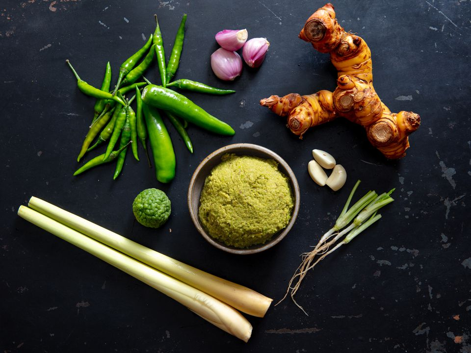 green curry paste in a small bowl with prominent ingredients surrounding it