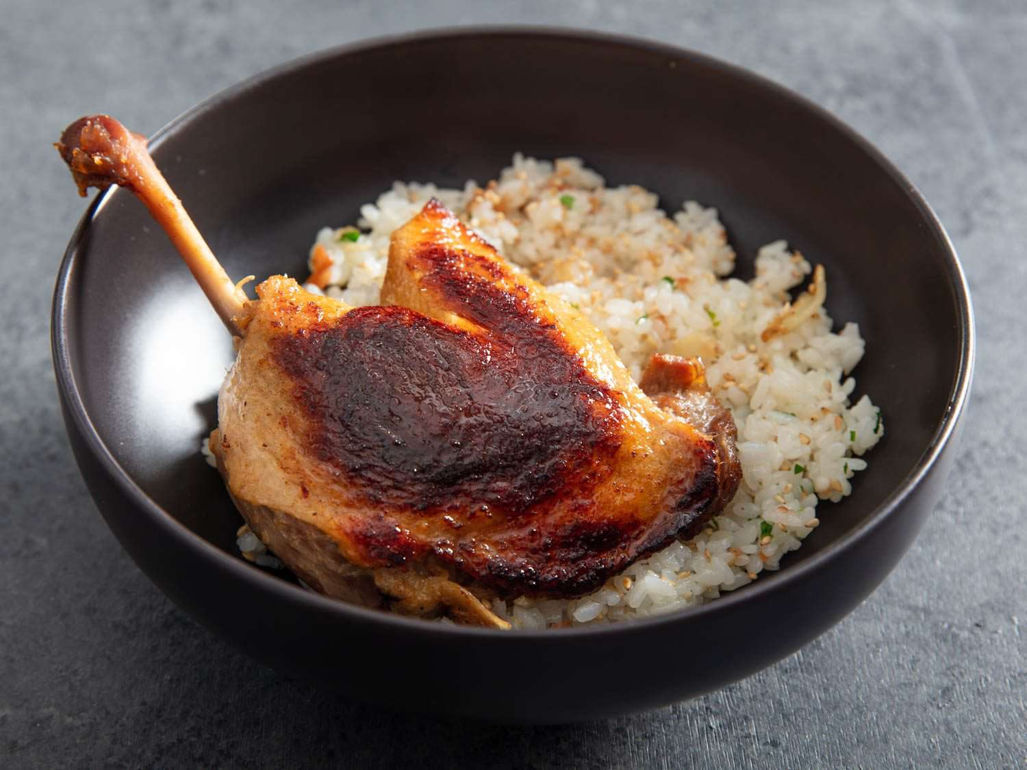Closeup of a bowl with a crisped leg of koji duck confit over rice.