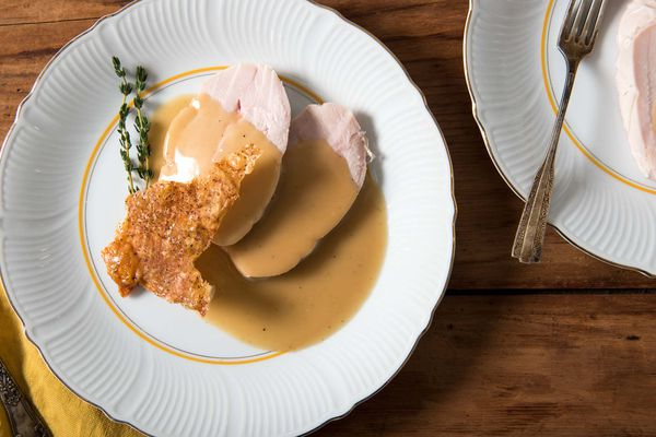 Sliced sous vide turkey breast with crisp skin cracklings and gravy on a white plate.