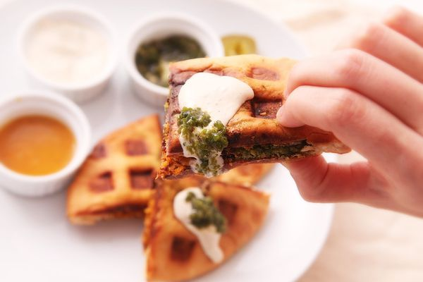 Waffled falafel sandwich dipped in tahina and green hot sauce.