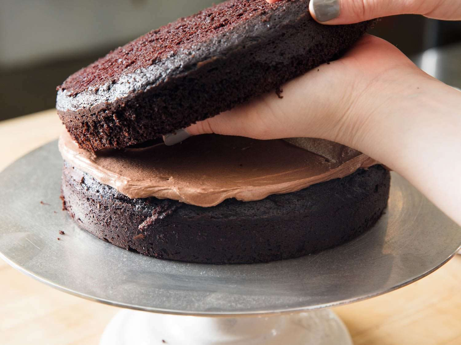 Laying down second layer of Devil's food cake on top of chocolate Swiss buttercream.