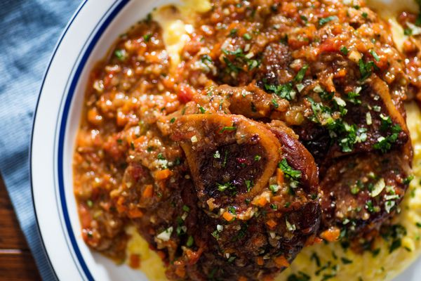 Close up photograph of a plate of osso buco and risotto alla milanese, garnished with gremolata.