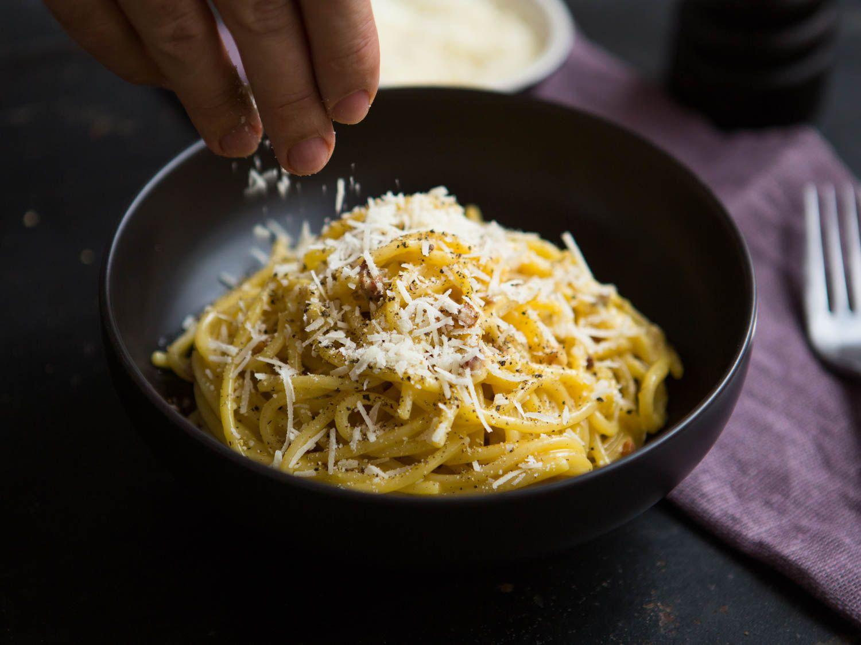 Sprinkling cheese on a bowl of spaghetti carbonara.